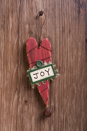 bell shaped: christmas heart shaped wooden decorations and christmas bell hanging on wooden background