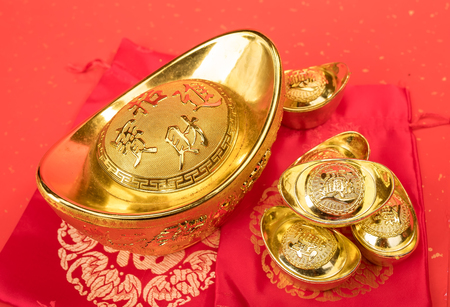 Chinese gold ingot mean symbols of wealth and prosperity.Chinese calligraphy Translation:good bless for money Stock Photo