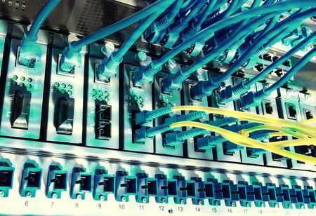 Fiber Optic cables connected to an optic ports and Network cables connected to ports Stock Photo