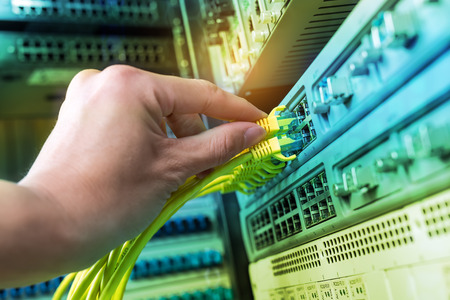 hand of administrator holding network cables connected to servers Stock Photo
