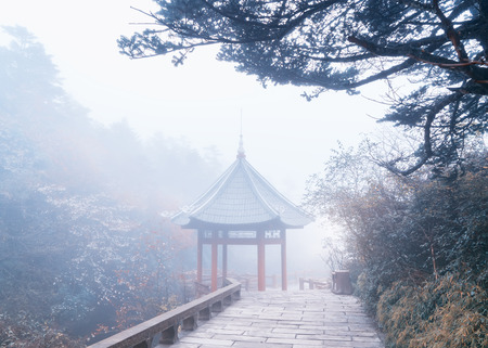 dampness: Traditional chinese pavilion in mist rain Emeishan,China Stock Photo