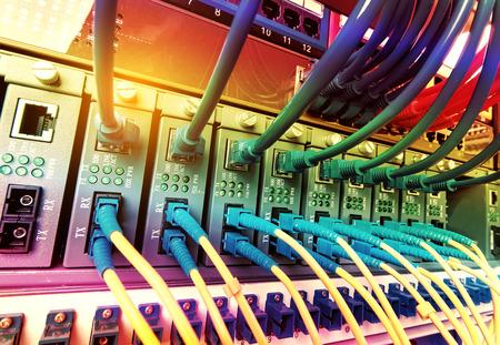 광섬유 케이블은 광 포트에 연결되고 네트워크 케이블은 포트에 연결됩니다. 스톡 콘텐츠