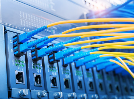tcp ip: Fiber Optic cables connected to optic ports and UTP, Network cables connected to ethernet ports. Stock Photo