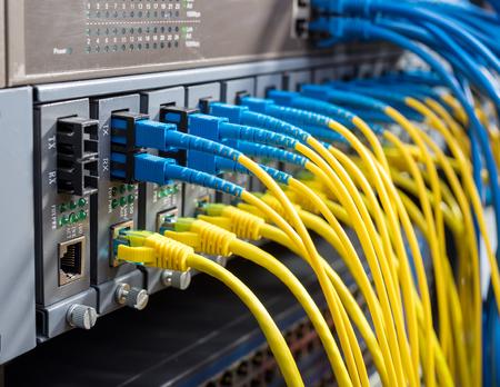 Cables de fibra óptica conectados a puertos ópticos y UTP, cables de red conectados a puertos. Foto de archivo