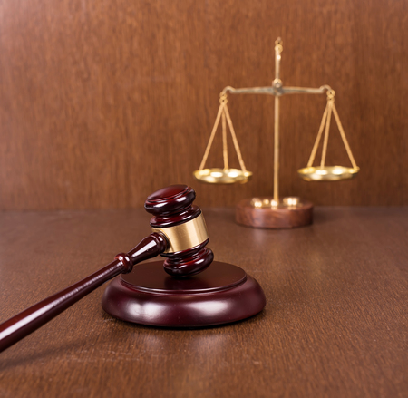 judicial proceeding: Wooden gavel with scales on wooden table, law concept