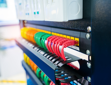 Server rack with internet patch cord cables connected to patch panel in server room