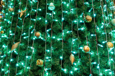 golden bubble and many lights hanging as christmas tree decoration new year fir tree branch