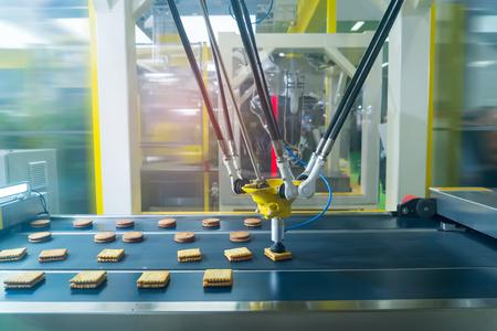 robot avec ventouses à vide avec convoyeur en production de biscuits dans une usine de fabrication pour l'industrie alimentaire
