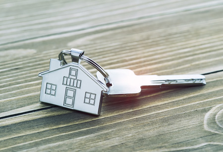 keychain with house symbol and keys on wooden background,Real estate concept Foto de archivo