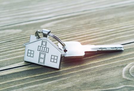 sleutelhanger met huissymbool en sleutels op houten achtergrond, onroerend goed concept Stockfoto