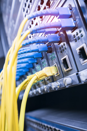 Fiber Optic cables connected to an optic ports and Network cables connected to ports Editorial