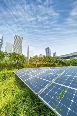 Planta de paneles solares renovables de energía ecológica con hitos del paisaje urbano Foto de archivo