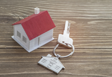 huis symbool sleutelhanger met sleutels op houten achtergrond. Vastgoedconcept