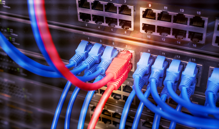 Network switch and cables in server room. Patch cords connected to router in data center. Horizontal technology background Stock Photo
