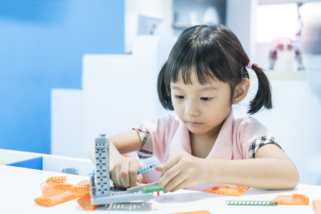 asian girl child playing with colorful plastic blocks indoor