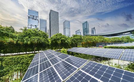 Paneles solares con paisaje urbano de ciudad moderna, concepto de energía renovable ecológica.
