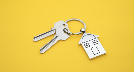 key chain with house symbol and keys on yellowbackground,Real estate concept Imagens