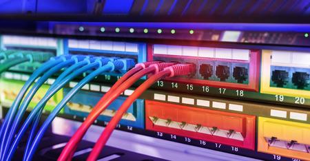 Rack de servidores con cables de cable de conexión a internet azul y rojo conectados al panel de conexión negro en la sala de servidores de datos