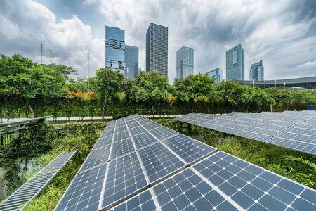 Planta de paneles solares renovables de energía ecológica con hitos de paisaje de edificios modernos urbanos