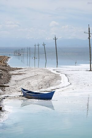 Salt Lake landscape with blue boat, named Chaka Salt Lake, is located in Qinghai Province, China.