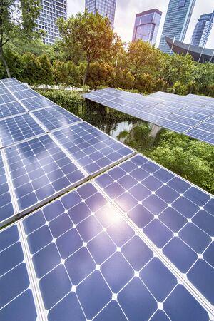 Ecological energy renewable solar panel plant with urban landscape