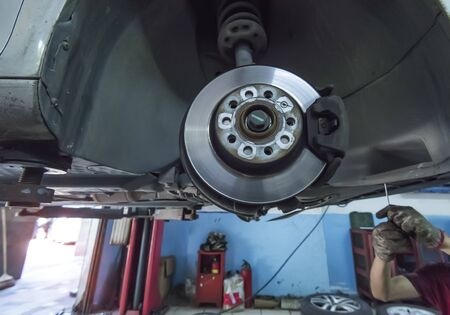 brake discs with caliper and brake pads in the car on a car lift in a workshop.