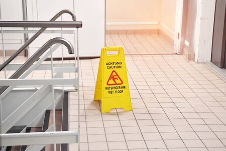 Yellow Caution wet floor sign on wet floor with Germany and English Language