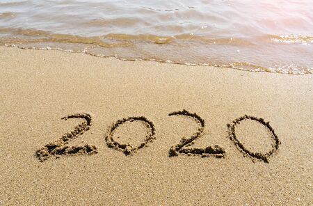 2020 year message handwritten in sand on beautiful beach background. New Years concept.