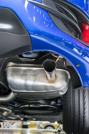 Close up horizontal shot of a blue car exhaust pipe.
