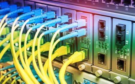 Fiber Optic cables connected to optic ports and UTP, Network cables connected to ports.