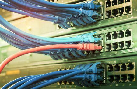 Rack de servidores con cables de cable de conexión a internet azul y rojo conectados al panel de conexión negro en la sala de servidores de datos Foto de archivo