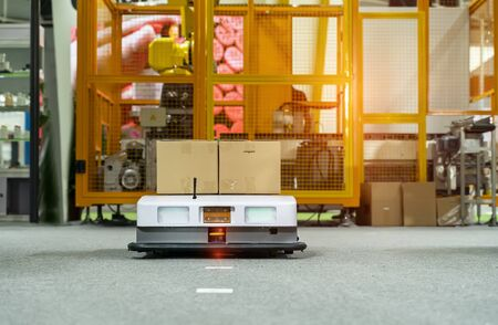 El coche robot de almacén lleva el montaje de la caja de cartón en la fábrica. Foto de archivo