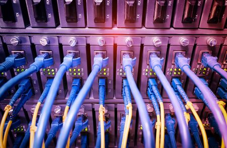 Fiber Optic cables connected to an optic ports and Network cables connected to ethernet ports