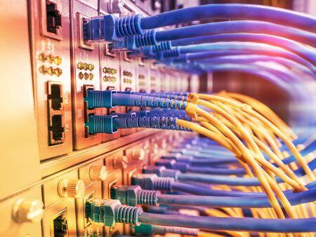 Glasfaserkabel, die mit einem optischen Port verbunden sind, und Netzwerkkabel, die mit Ethernet-Ports verbunden sind