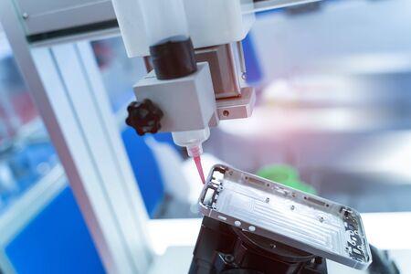 Robot tenant l'injection de seringue de colle dans l'usine de téléphonie mobile Banque d'images