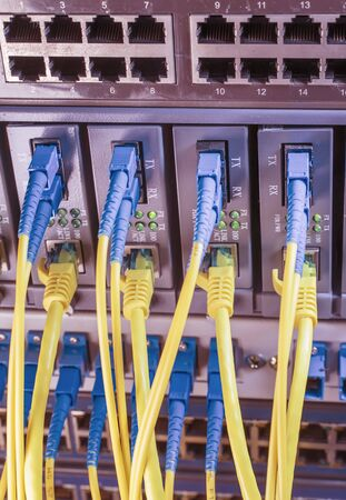 Fiber Optic cables connected to optic ports and UTP and Network cables connected to ethernet ports