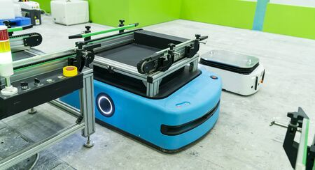 warehouse robot car carries cardboard box assembly in factory Banque d'images