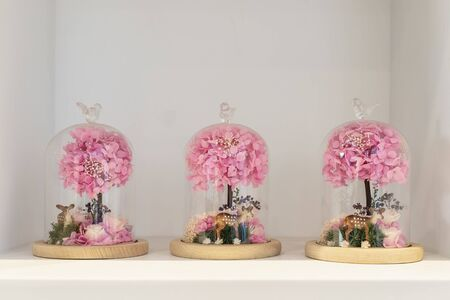 fresh flowers under a glass cover on a stand on a wooden stand. Floral decoration of a festive wedding table. Standard-Bild