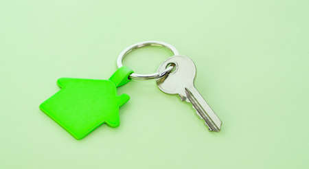 key chain with house symbol and keys on green background,Real estate concept