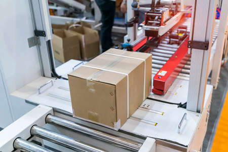 cardboard box of product packaging is moving on conveyor belt of automatic packing machine in the manufacturing factory