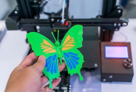 hand with object in shape of butterfly toy printed on 3d printer