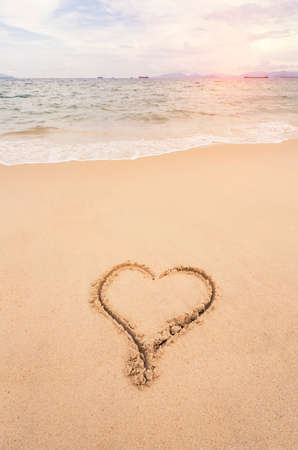 heart drawn in the sand on the beach. Romantic design element.