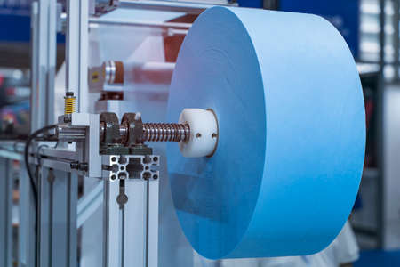 non woven material on automatic machine for the manufacture of medical masks with nanofiber. Coronavirus and Covid-19 Protection