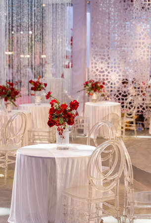 luxury wedding decor with flowers and glass vases and number of setting on round tables