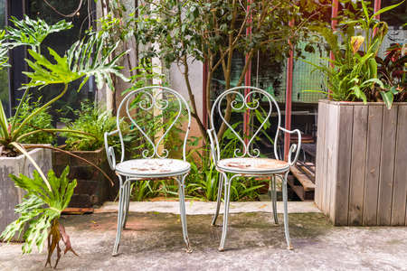 old steel chairs standing in a beautiful garden at sunny day. Banco de Imagens