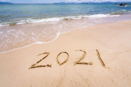 2021 year message handwritten in sand on beautiful beach background. New Years concept.