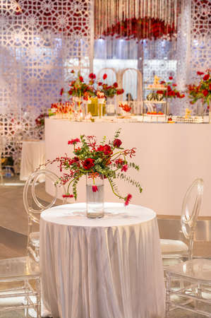 luxury wedding decor with flowers and glass vases and number of setting on round tables Archivio Fotografico