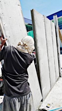 precast: The site worker installing the precast concrete wall panel