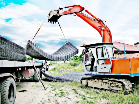 Excavator busy unloading the wire mesh from the trailer