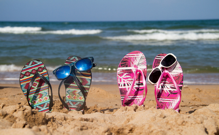 flip flops with sunglasses on the beach Archivio Fotografico - 118444259